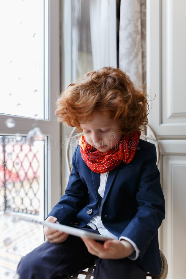 Little redhead boy uses a tablet PC royalty free stock images