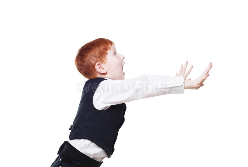 Little redhead boy in vest, stops something with hands royalty free stock photo
