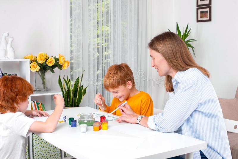 Little redhead boys with a nanny or mother or teacher sit at the table and paint with colors royalty free stock images