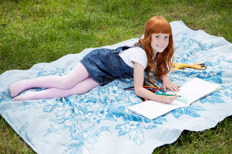 Little redhead girl drawing royalty free stock photography