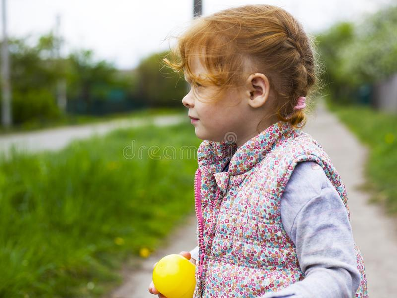 Little redhead girl with pigtails looks away stock images