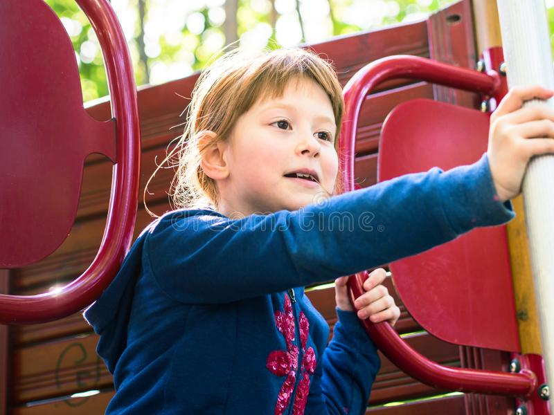 Little redhead girl playing on playground stock images