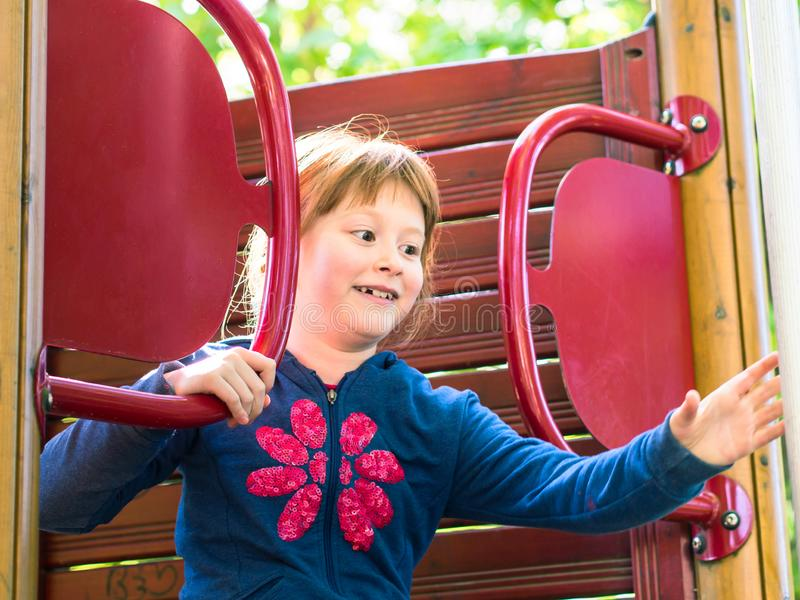 Little redhead girl playing on playground royalty free stock photo
