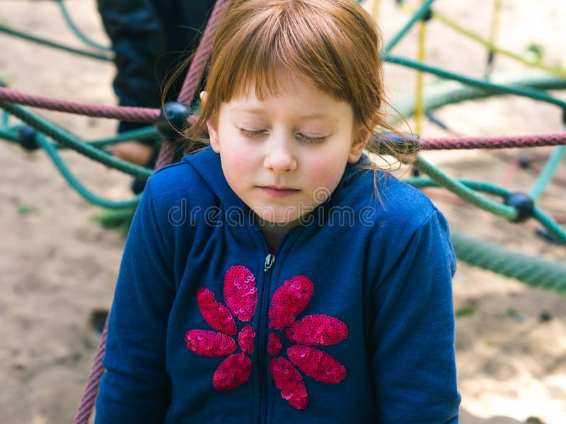 Little redhead girl playing on playground stock photos
