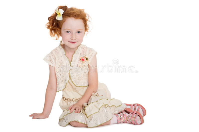 Little redhead girl sitting stock images