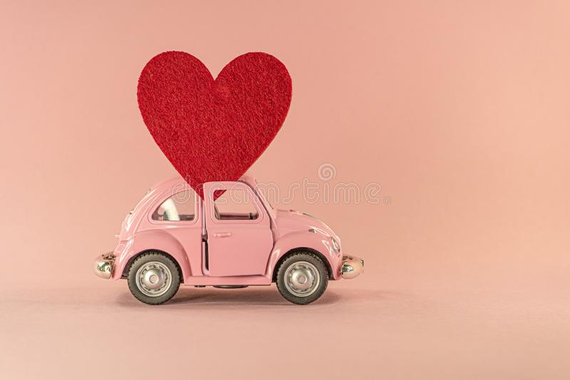 Little retro toy model car with red heart on pastel pink background. Love, friendship, valentines day, delivery royalty free stock photography