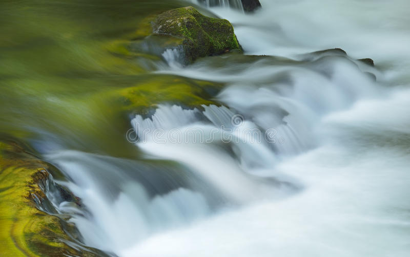 Little River Cascade. Captured with motion blur and illuminated by reflected color from sunlit spring foliage and blue sky overhead, Great Smoky Mountains royalty free stock images