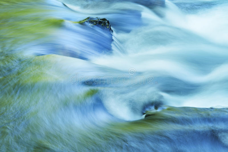 Little River Rapids. Captured with motion blur and illuminated by reflected color from sunlit spring foliage and blue sky overhead, Great Smoky Mountains stock photos