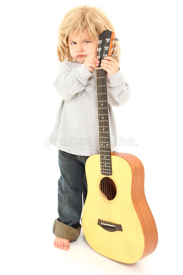 Little Rocker Guitar Player. Adorable three year old american boy with long rocker hair and accoustic guitar over white background stock photos