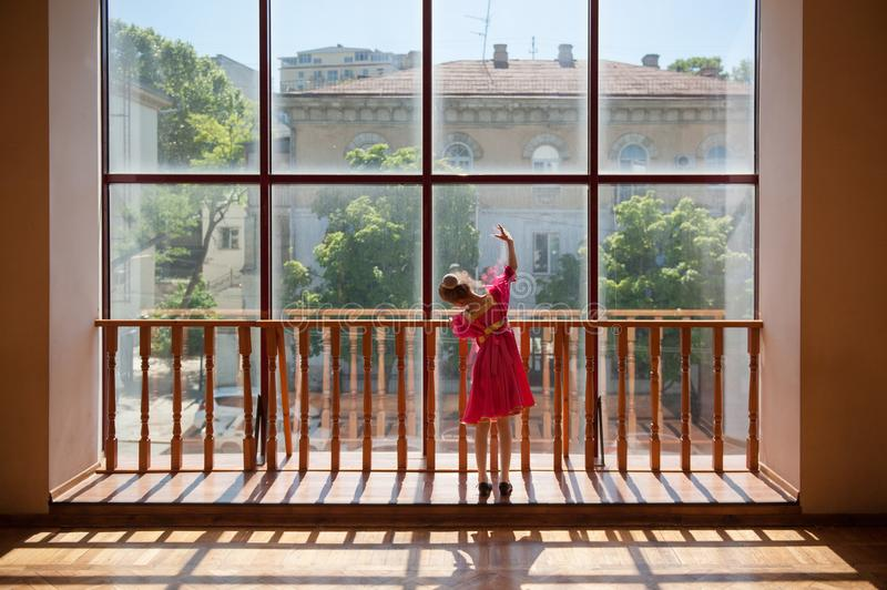 Little russian ballerina girl in traditional dress barre exercise near window stock photo
