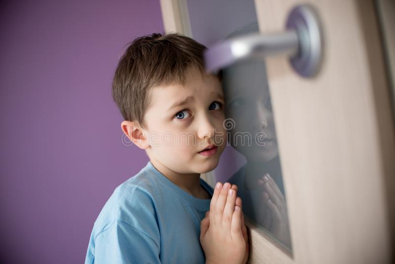 Little sad boy overhears fight of his parents - B&W. Little boy overhears fight of his parents through the door - black and white stock image