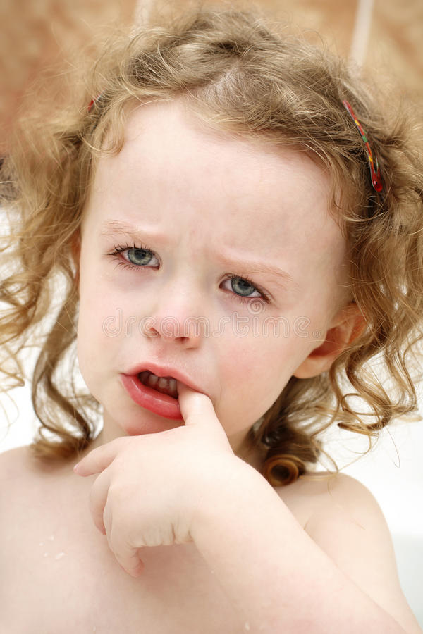 Little sad girl in the bath. Little nasty child crying in the bath stock images
