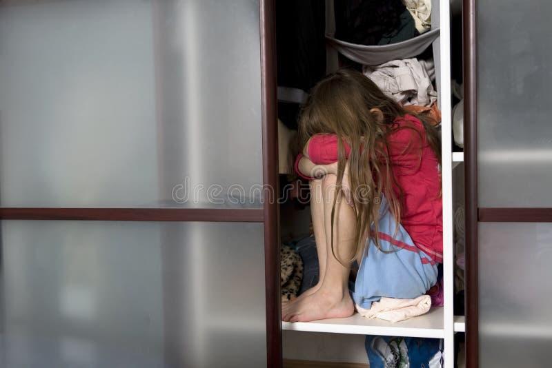 Little sad girl sitting inside wardrobe stock images