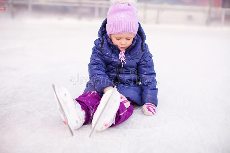 Little sad girl sitting on a skating rink after. The fall. This image has attached release royalty free stock photo