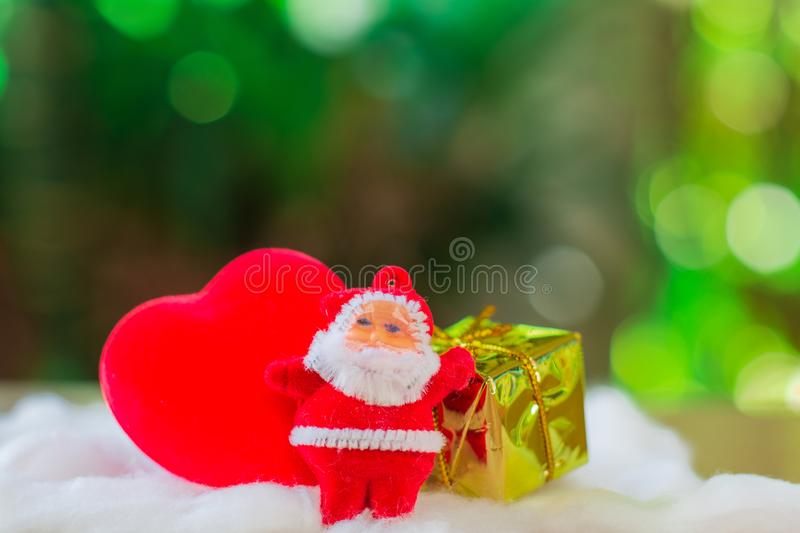 Little santa claus with red heart shape and group of giftbox on white cotton with green boken bacjground. Christmas concept stock photography