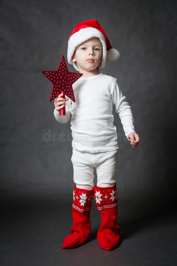 Little Santa with red star. Cute little Santa with red star, gray background stock photos