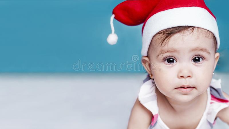 Little Santa. 1-year-old baby girl in Santa Claus hat. Merry Christmas. Adorable middle-eastern girl in Santa cap stock photo