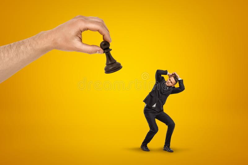 Little scared businessman covering his head with hands to protect from huge hand holding black chess pawn on yellow stock images