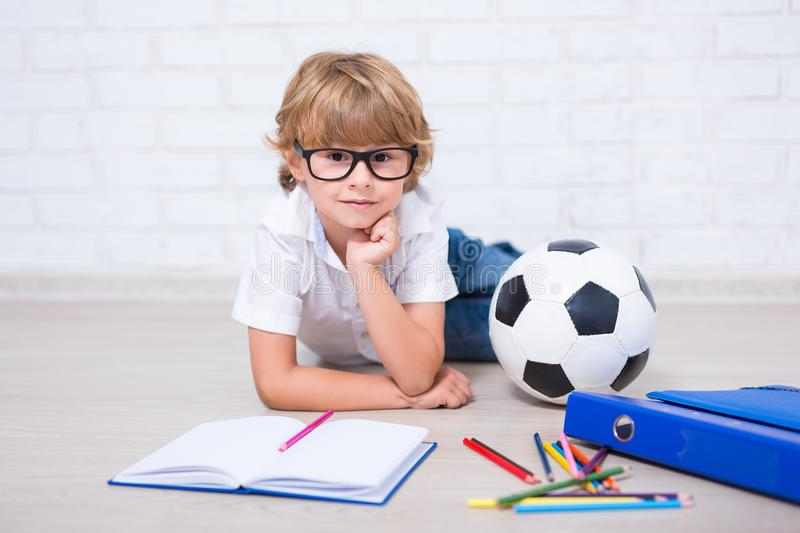 Little school boy in glasses doing homework and thinking about s. Omething st home royalty free stock image