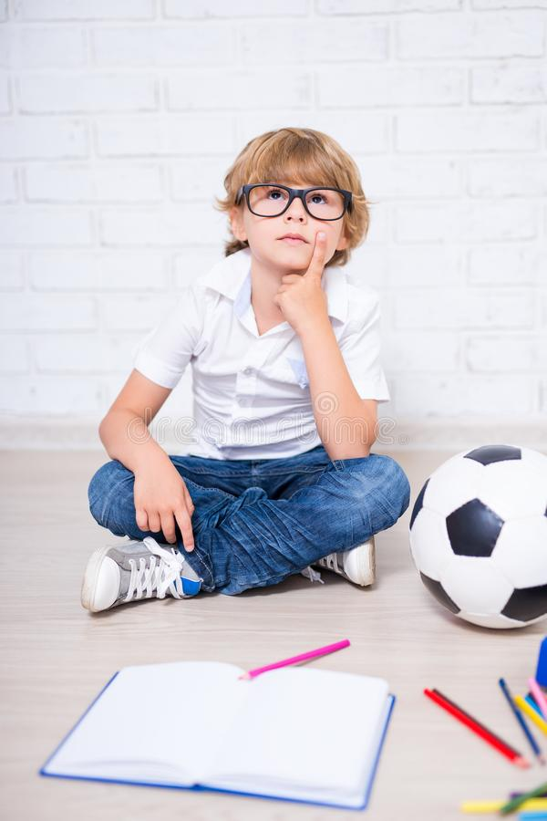 Little school boy in glasses sitting on the floor, doing homework and thinking about something. Little school boy in glasses sitting on the floor, doing homework royalty free stock image