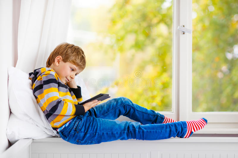 little school boy reading book or ebook by window stock photos