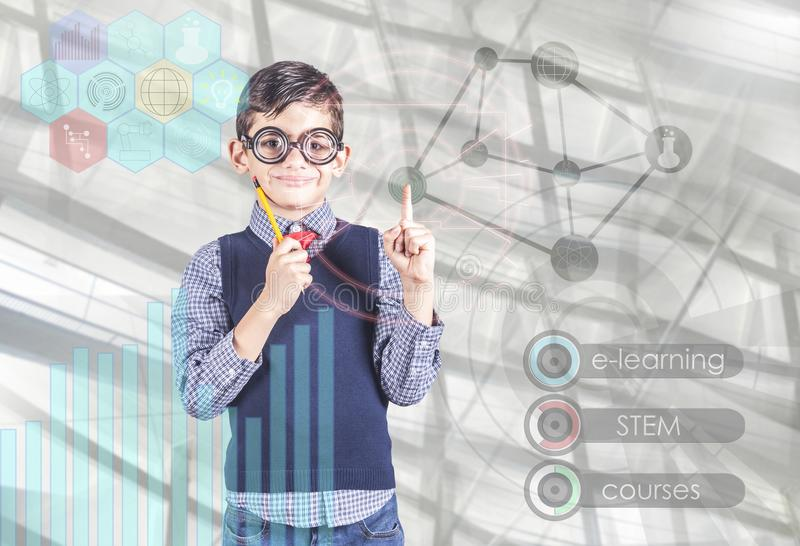 E-learning and futuristic STEM education technology concept. Little school boy using digital hud interface and icons stock photos