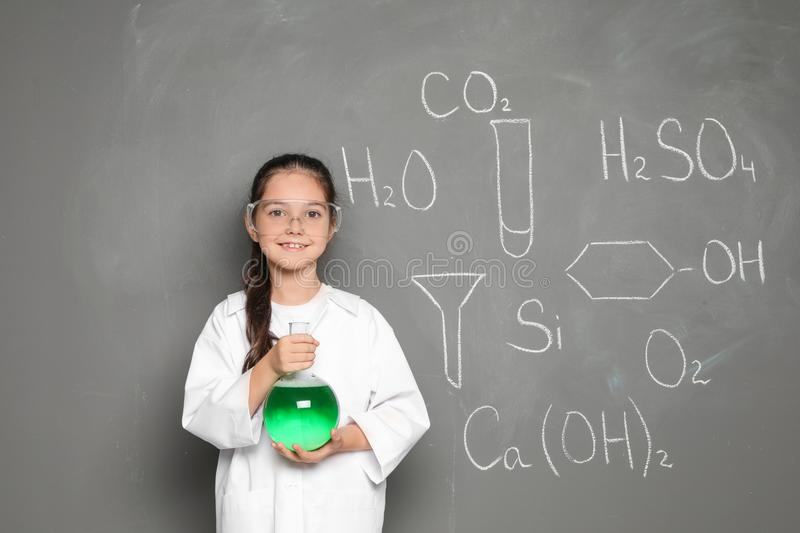 Little school child in laboratory uniform with flask. Of liquid and chemical formulas on grey background royalty free stock image