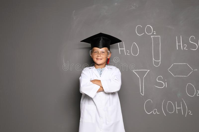Little school child in laboratory uniform with graduate cap stock photos