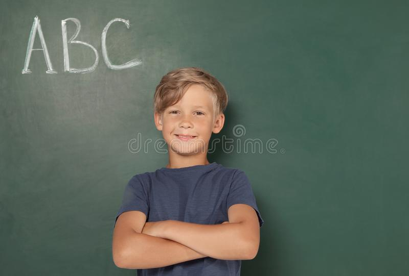 Little school child near chalkboard with ABC. Little school child near chalkboard with letters ABC royalty free stock photo