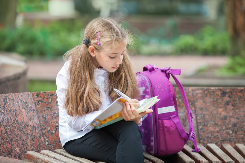 Schoolgirl with a backpack and book outdoors. Education and learning concept royalty free stock photography