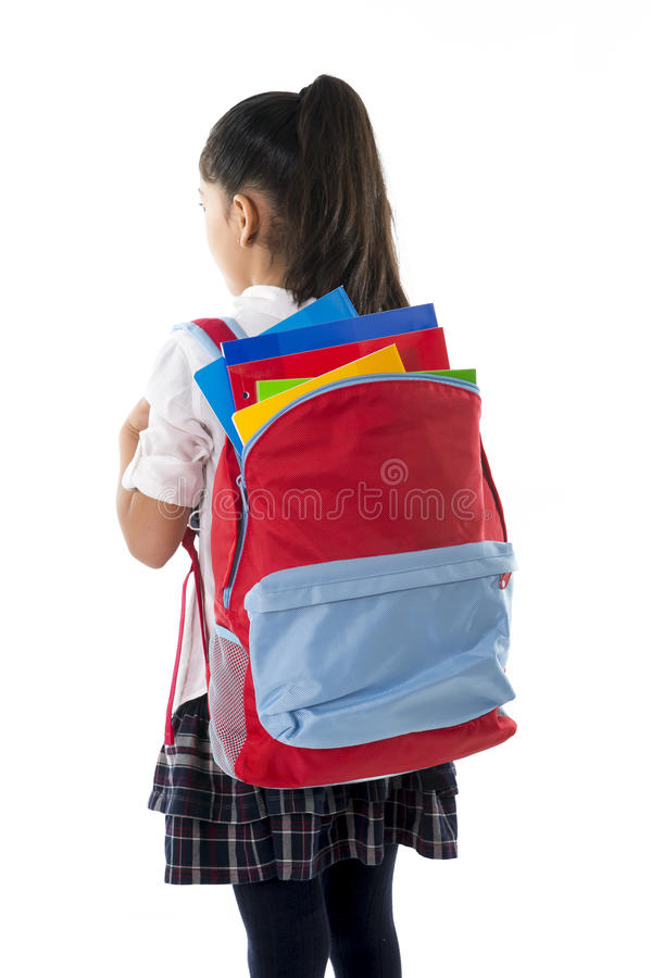 Little school girl carrying very heavy backpack or schoolbag full royalty free stock photography