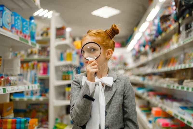 Little school girl looks through magnifying glass stock photo