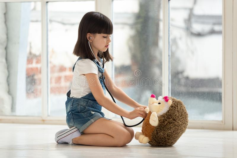 Little school girl playing with toy, pretending to be doctor. stock photography