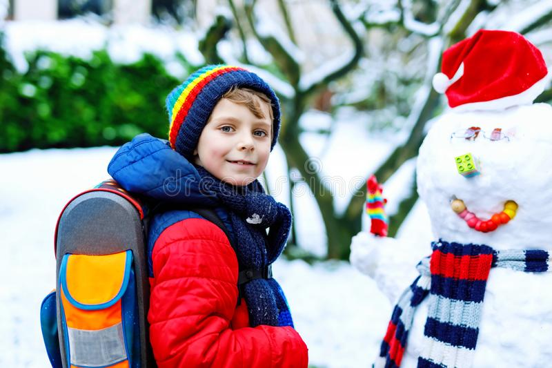 Little school kid boy in colorful clothes, with glasses and backpack having fun with snowman after elementary school end stock photography