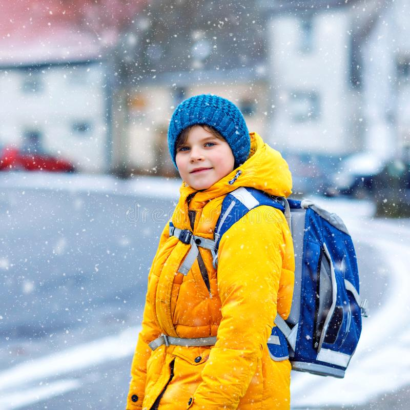 Little school kid boy of elementary class walking to school during snowfall. Happy child having fun and playing with royalty free stock photography