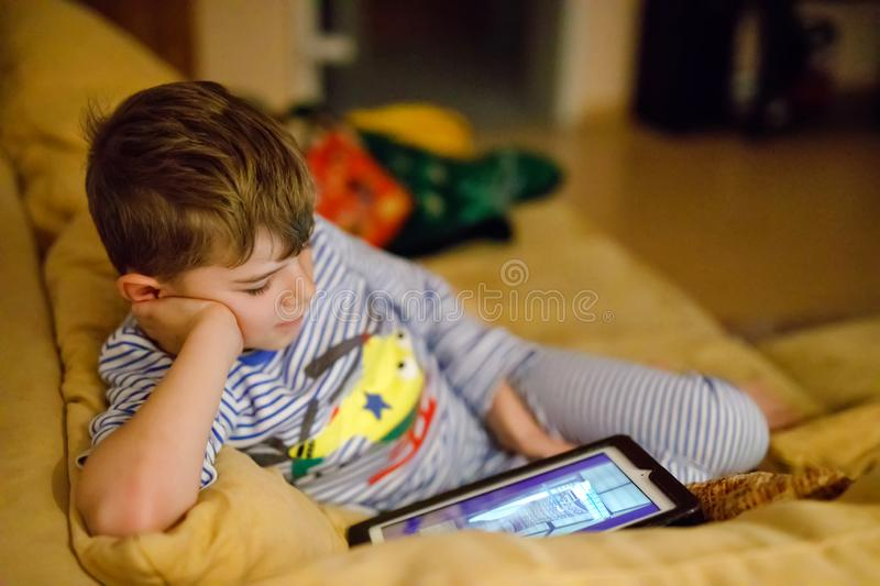 Little school kid boy making homework with tablet. Schoolchild reading and learning with computer, searching for. Information in internet and looking cartoons royalty free stock photo