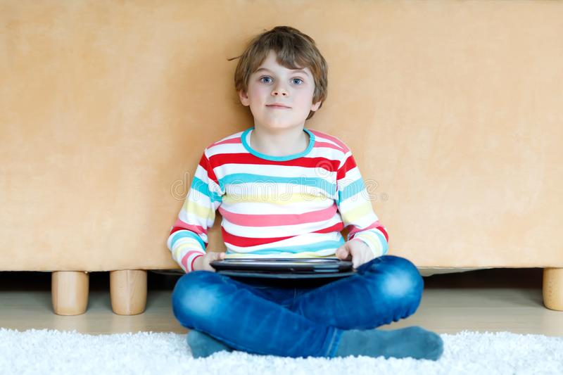 Little school kid boy making homework with tablet. Schoolchild reading and learning with computer, searching for royalty free stock photo