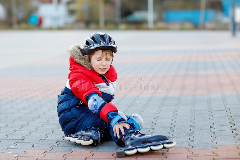 Little school kid boy skating with rollers in the city. child in protection safety clothes. Active schoolboy making. Sports and learning to skate on inline royalty free stock image
