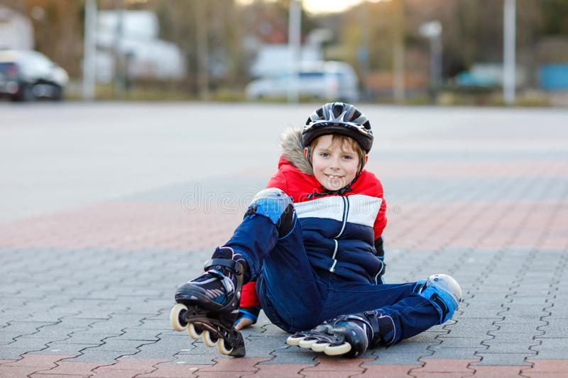 Little school kid boy skating with rollers in the city. child in protection safety clothes. Active schoolboy making. Sports and learning to skate on inline stock photo