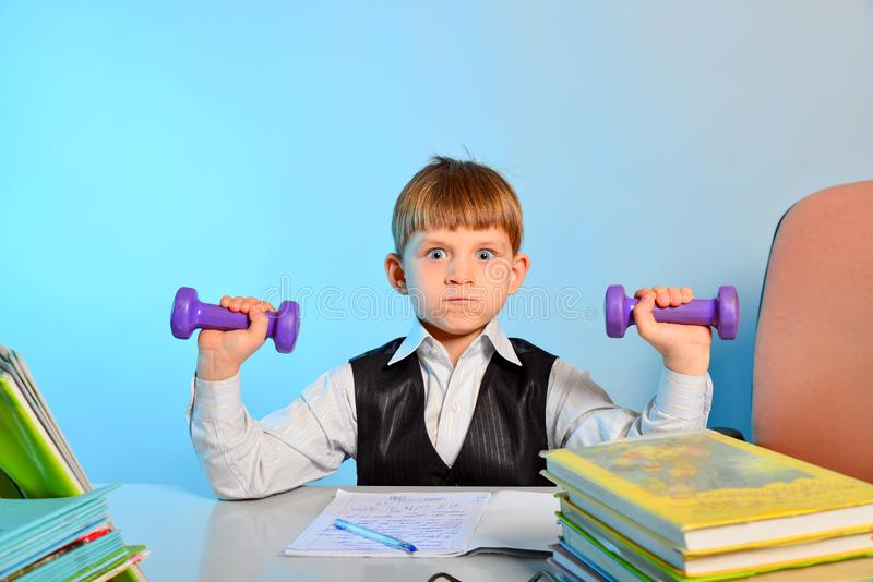 The little schoolboy is engaged in dumbbells among notebooks and textbooks at his desk at school in the classroom stock photography