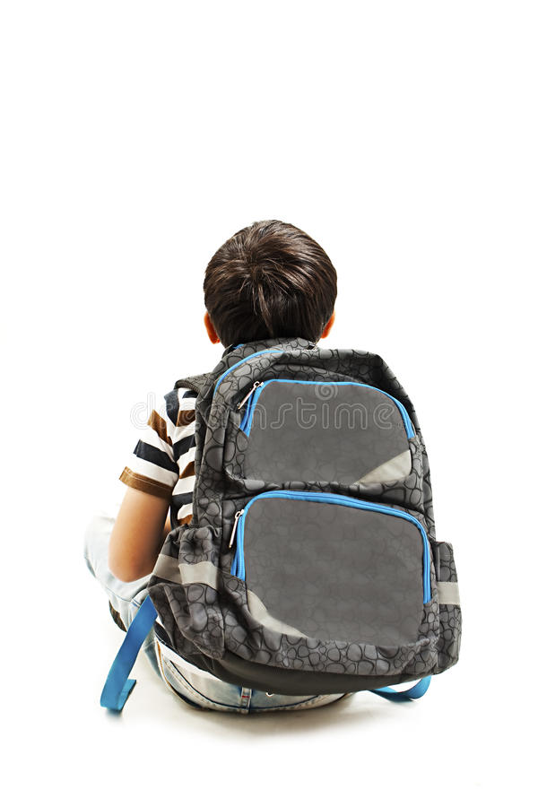 Little schoolboy with schoolbag looking at empty copy space. Rear view stock image