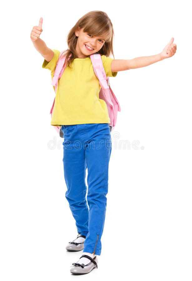 Little schoolgirl with a backpack. Showing thumb up sign, isolated over white royalty free stock images