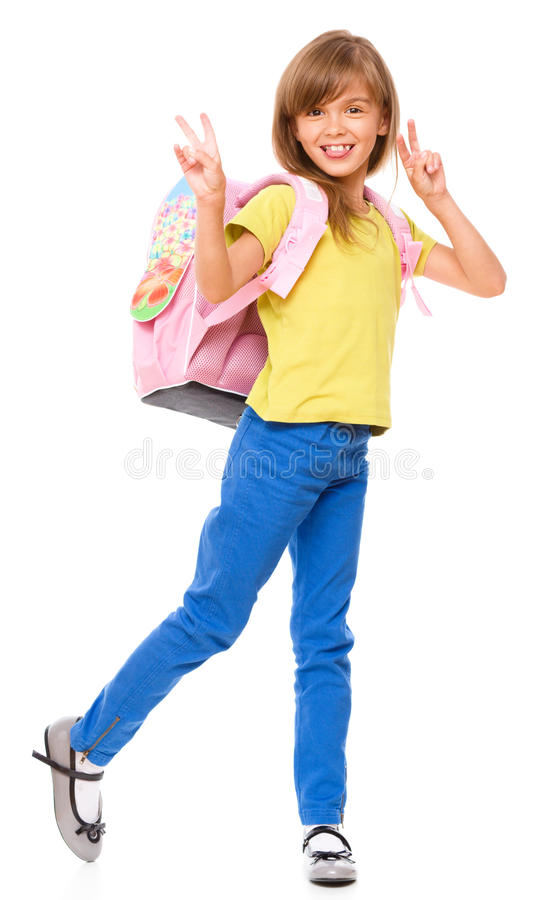 Little schoolgirl with a backpack. Showing victory sign, isolated over white stock photography