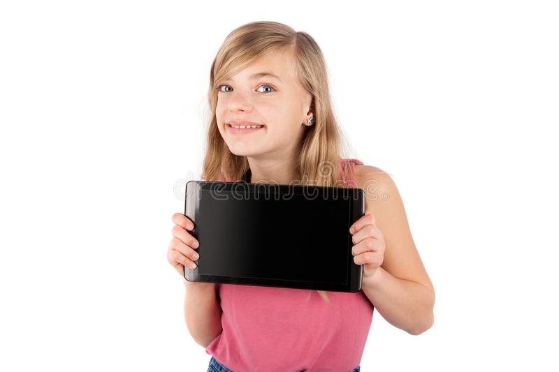 Little schoolgirl holding a tablet pc device with blank screen. stock images
