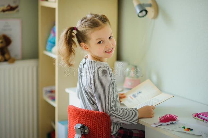 The little schoolgirl performs homework. stock photo