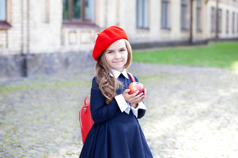 Little schoolgirl in a red beret and dress with lunch near the school. preschool child with an apple and a backpack on his first d. Ay at school or kindergarten stock photography