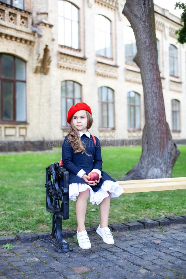 Little schoolgirl in a red beret and dress with lunch near the school. preschool child with an apple and a backpack on his first d. Ay at school or kindergarten stock photo
