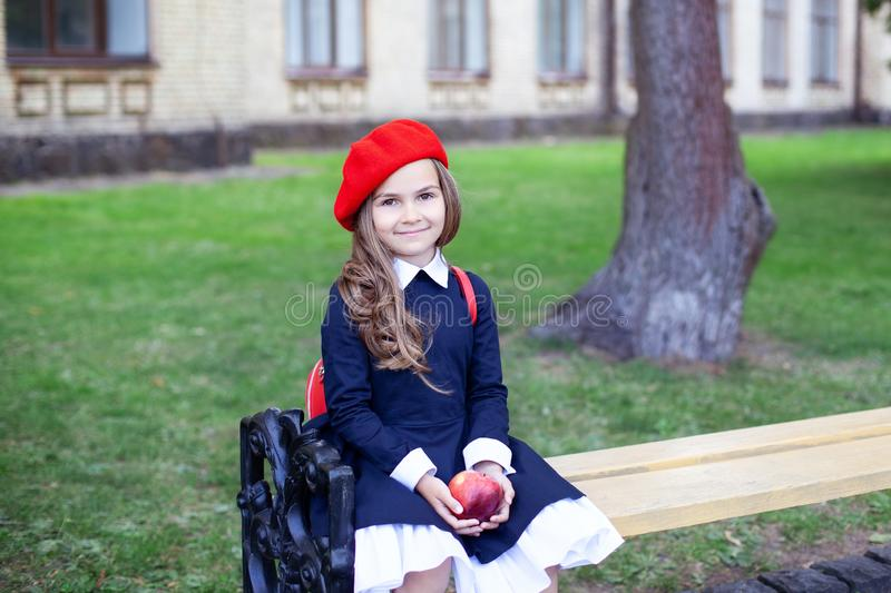 Little schoolgirl in a red beret and dress with lunch near the school. preschool child with an apple and a backpack on his first d. Ay at school or kindergarten royalty free stock photography