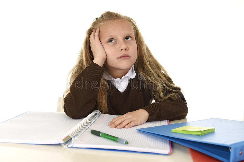 Little schoolgirl sad and tired looking depressed suffering stress overwhelmed by load of homework. Sweet little schoolgirl sad and tired looking depressed royalty free stock photography