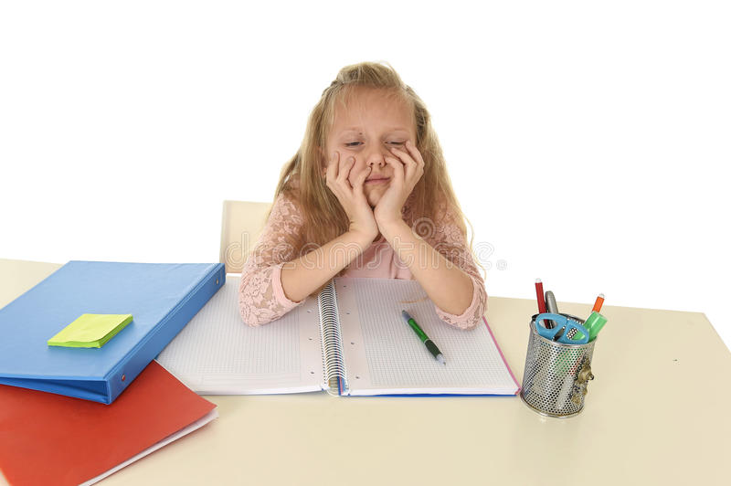 Little schoolgirl sad and tired looking depressed suffering stress overwhelmed by load of homework. Sweet little schoolgirl sad and tired looking depressed stock photo